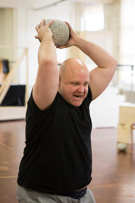 A man in a black t shirt angrily holds a rock aloft, ready to throw