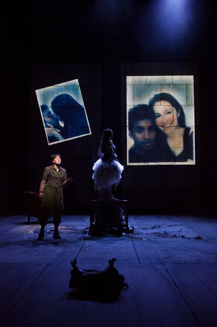 Young woman standing on a table looking at two pictures of herself and young man projected on the back wall of the theatre