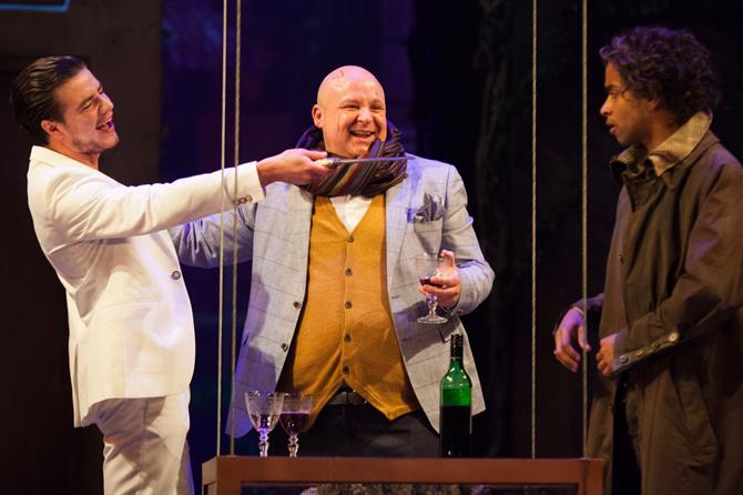 A young man in a white suit laughing with an older bald man pointing a knife at a younger man in a green trenchcoat