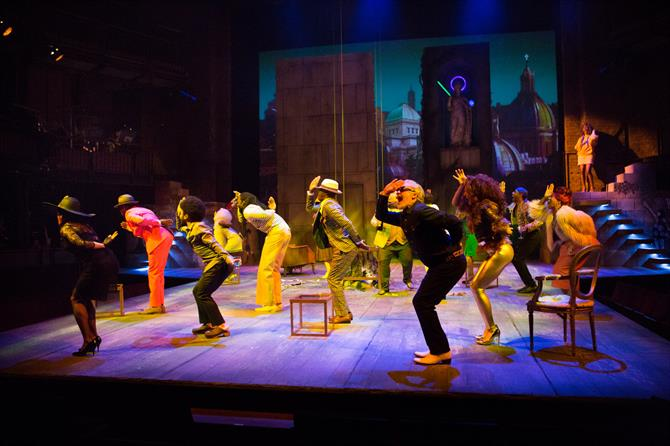 The cast of Cymbeline dancing in sync on a colourfully lit stage