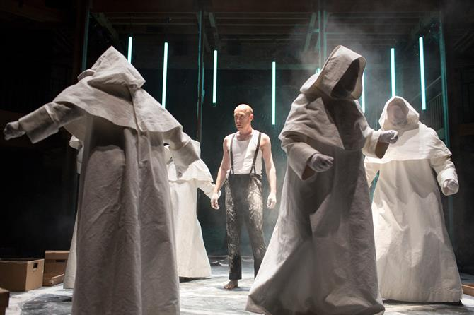Sandy Grierson as Doctor Faustus is surrounded by sinister hooded figures in white robes