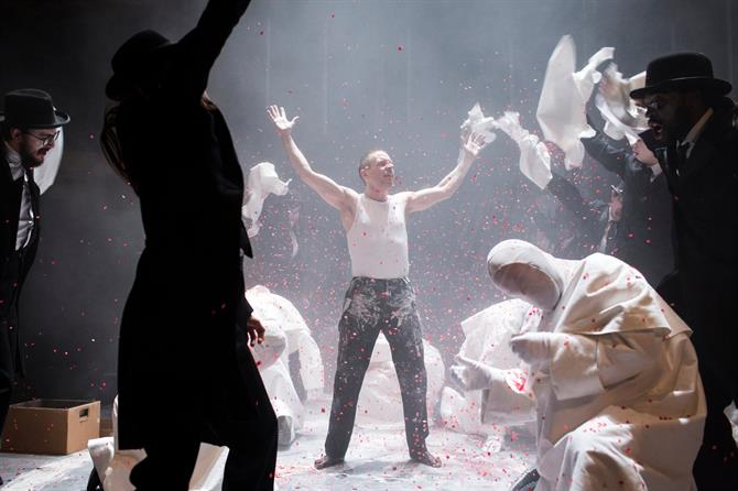 Oliver Ryan as Doctor Faustus  holds his hands up as red confetti falls from above
