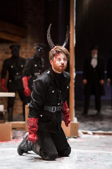 Tom McCall as Benvolio in a black military suit, red rubber gloves and with dark horns