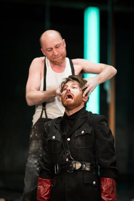 Doctor Faustus squeezes Benvolio's head