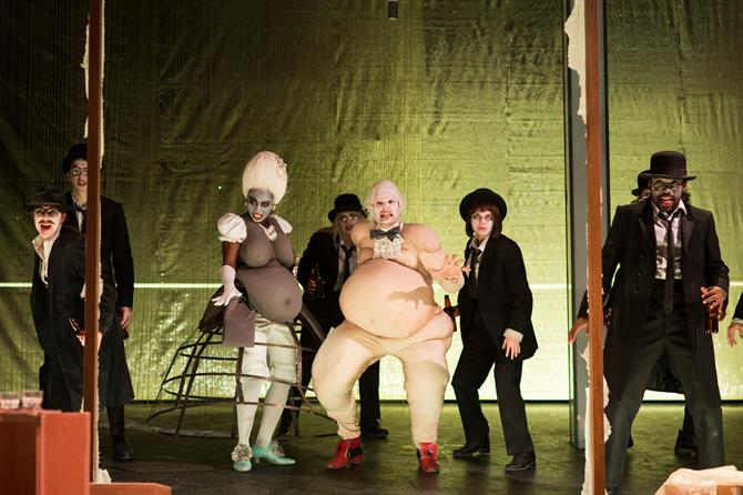 The Company of Doctor Faustus in performance, including two characters in grotesque fat suits
