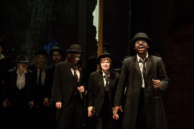 The Company of Doctor Faustus in performance, wearing dark suits and hats