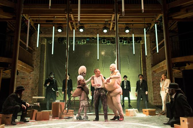 The Company of Doctor Faustus in performance - two characters in fat suits embrace a cowering man