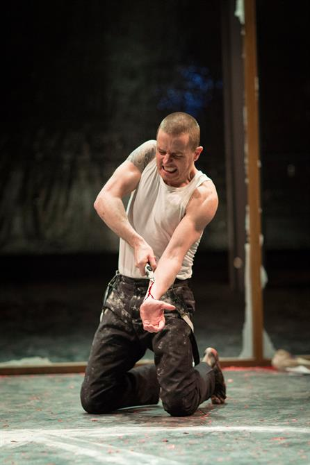 Oliver Ryan as Doctor Faustus draws a penknife up his arm, leaving a trail of blood