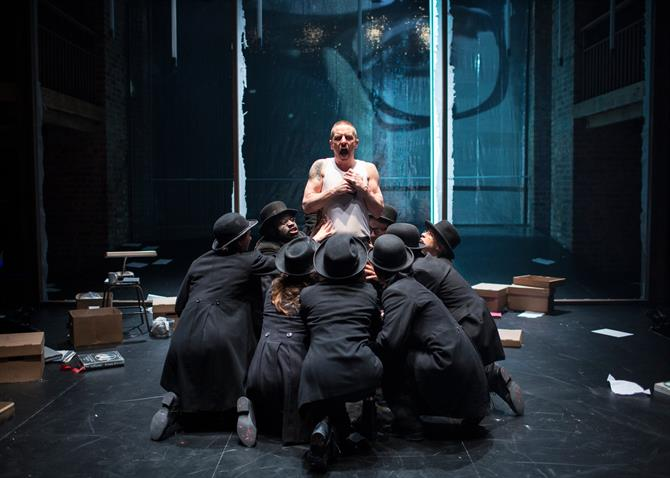 Oliver Ryan as Doctor Faustus with people in suits and hats kneeled around him