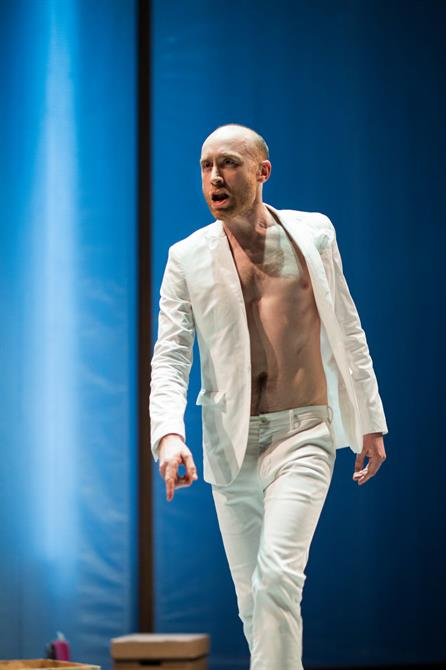 Sandy Grierson as Mephistophilis, wearing a white suit without a shirt