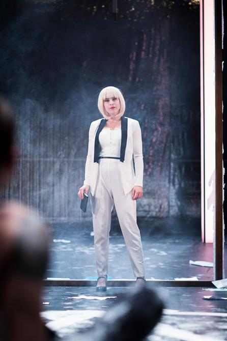 Eleanor Wyld as Lucifer, wearing a fitted white suit and a blonde wig