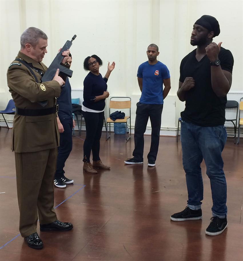 The cast of Hamlet in the rehearsal room learning to handle a gun