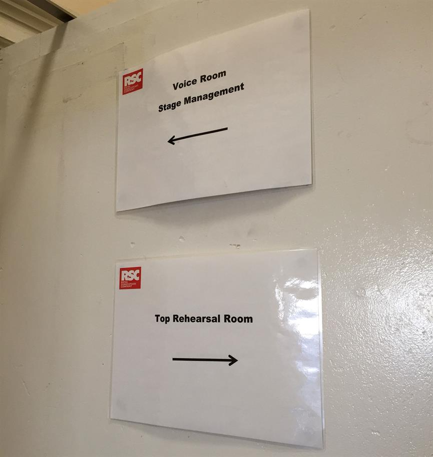 Paper signs tacked to a door, pointing the way to the Top Rehearsal Room and Voice Room