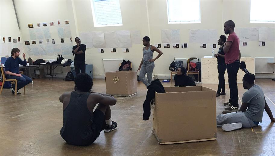 The cast of Hamlet seated on the floor with some large cardboard boxes containing costumes