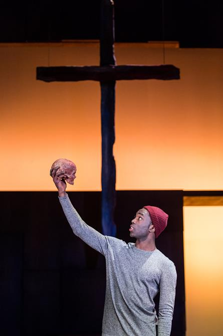 A huge crucifix hangs behind Hamlet, who is holding a skull above his head and speaking to it