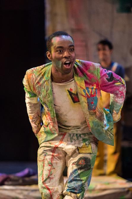 Hamlet running and shouting, wearing a suit covered in graffiti