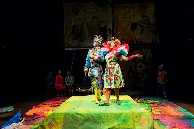 The Player king and queen parade across a bright stage, in fantastical costumes