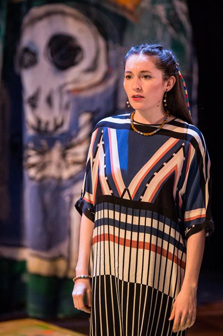 Guildenstern looks anguished, wearing a geometrically patterned dress