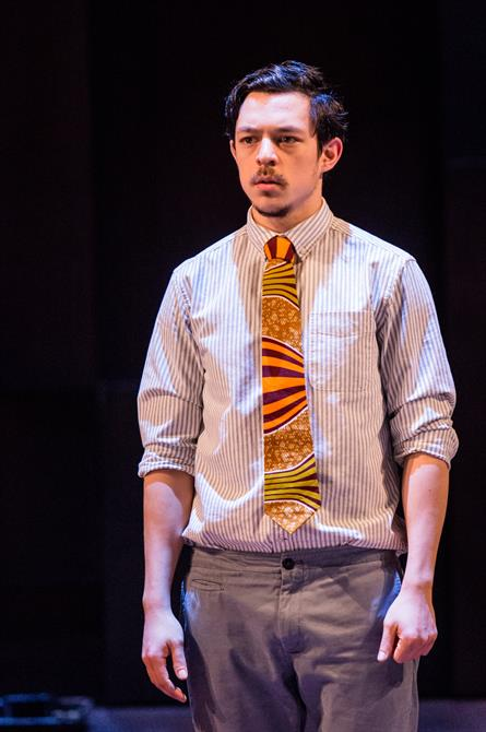 Rosencrantz stands looking awkward and angry, wearing a striped shirt and bold tie