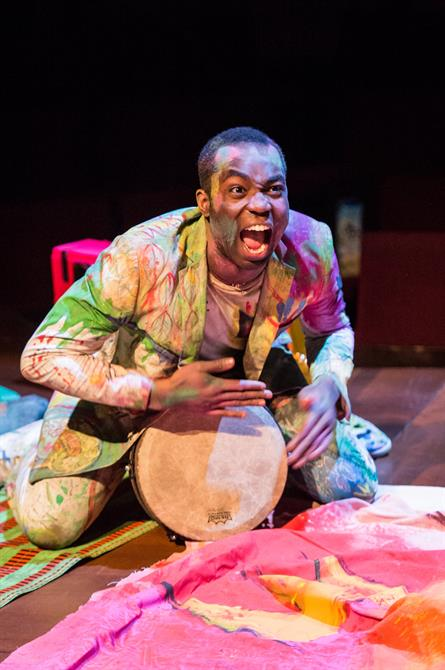 Paapa Essiedu as Hamlet in Hamlet, wearing a paint stained jacket and banging on a drum