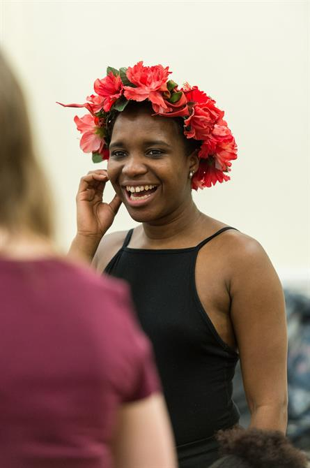 A woman laughing wearing a flower headband