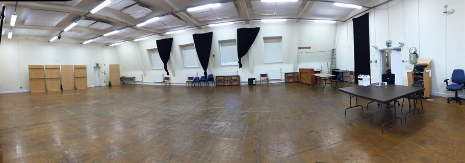 Wide shot of the empty rehearsal room for Hamlet - a big empty room with a few pieces of furniture around the outside
