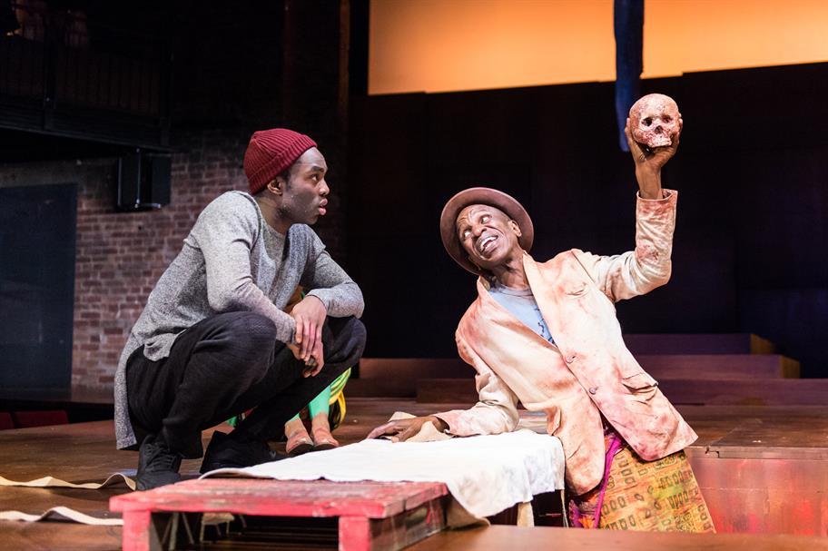 Hamlet looks on as the Gravedigger holds up a skull.