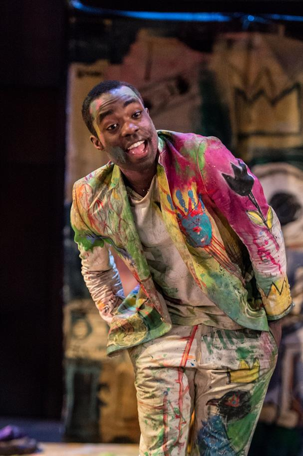 Paapa Essiedu as Hamlet leaning forward wearing a jacket and trousers covered in paint