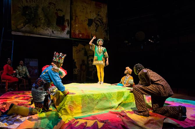 Four people in bright costumes crouch around a small stage, while a Player proclaims from the centre