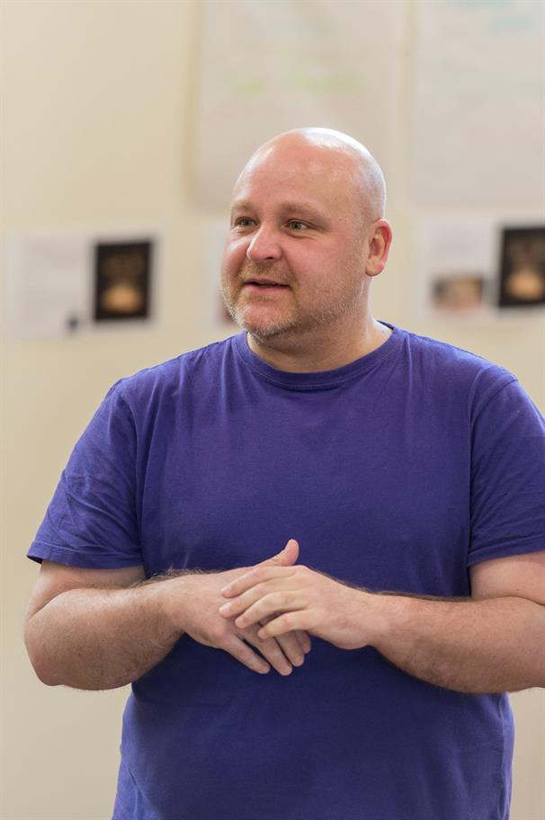 Byron Mondahl wearing a purple T-shirt with hands folded in front of him