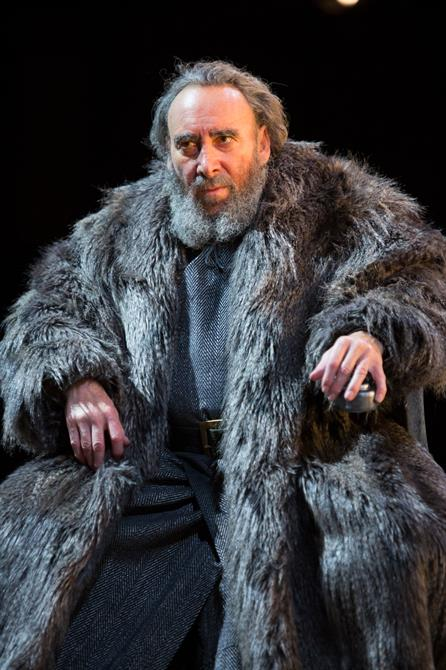 King Lear sits looking serious in his fur coat