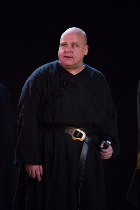 Byron Mondahl as Oswald, he is dressed in a black robe with a sword in his belt