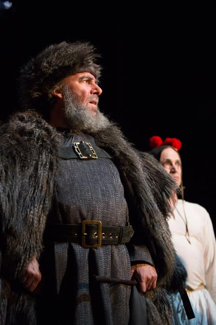 King Lear is dressed in his fur coat and hat, his fools is in the background