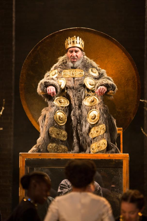 King Lear is dressed in his finery sitting on his high throne