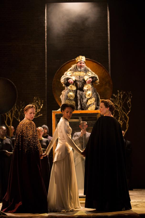 King Lear sits high up on a throne in a fur coat and crown looking down at his daughters who are looking behind them