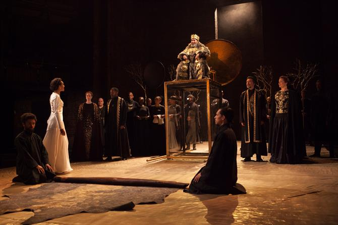 King Lear sits atop his high throne looking down at Cordelia. The are surrounded by courtiers.