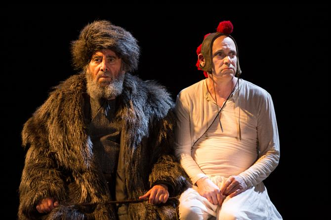 King Lear, dress in fur coat and fur hat, sits next to his fool - both look fed up