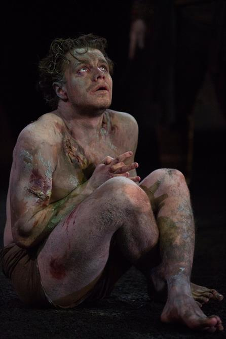 Edgar/Poor Tom sits cross legged looking to the sky. He is wearing a loin cloth and is muddy and covered in cuts and bruises