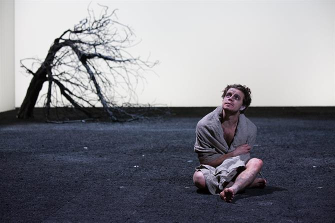 Edgar/Poor Tom sits cross legged with a blanket round his shoulders. There is a battered tree in the background.