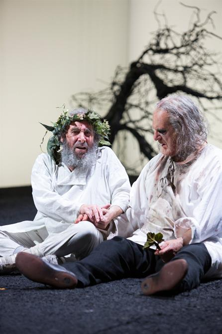 Two old men sit on the floor, King Lear comforts Earl of Gloucester. Both look dishevelled