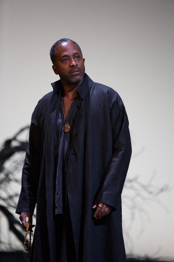 Clarence Smith wearing a long black coat, wearing a brown pendant and holding a necklace in his right hand