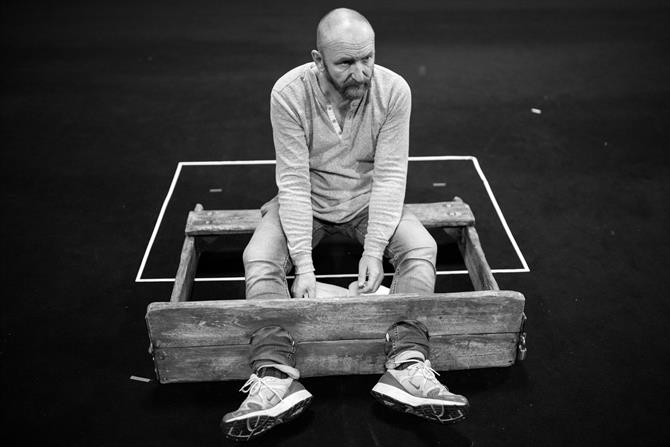 Antony Byrne in rehearsal for King Lear with his legs in the stalls