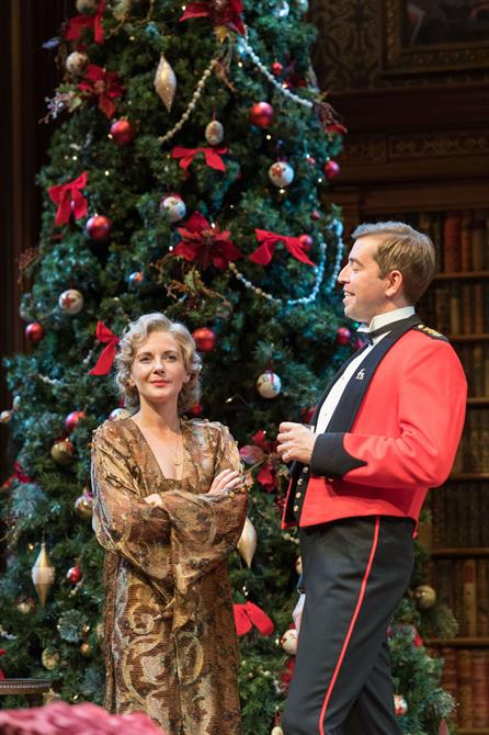Beatrice is a brown robe with arms folded and Benedick in military uniform standing in front of a Christmas tree