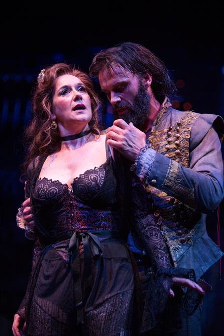 A woman in a black basque is embraced by a bearded man