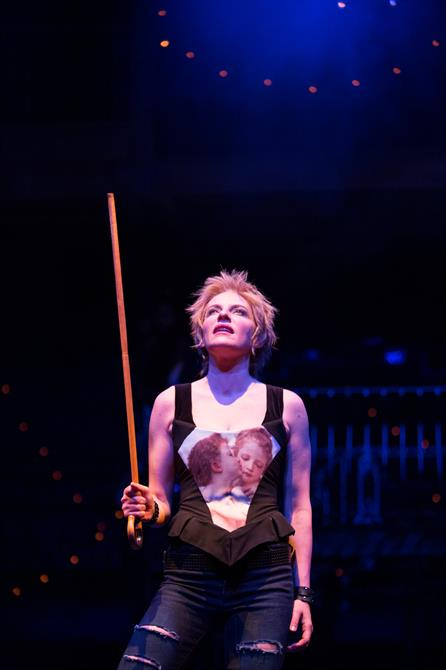 A woman with short blond hair holding a cane aloft