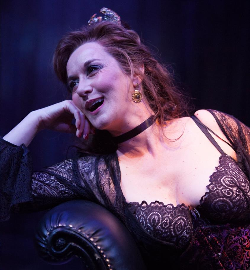 Actor in The Rover laughing in a black corset