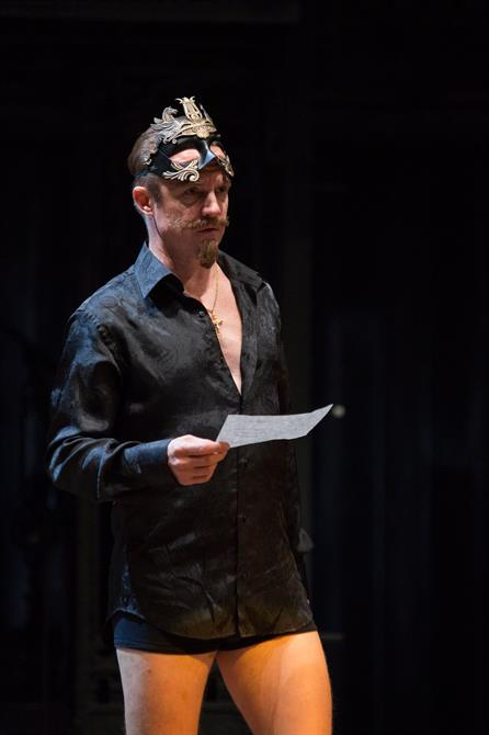 A man with a mask on his head, holding a piece of paper, wearing just a shirt