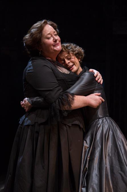 A woman in a black dress embracing a younger woman in a grey silk dress
