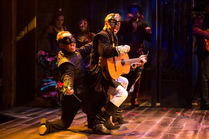 A man playing a guitar sits on the knee of another man in mask, holding a red rose