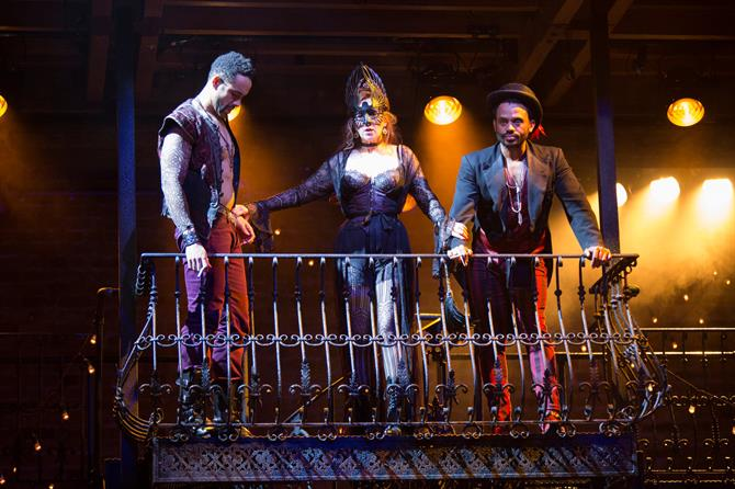 Two men and a woman in a mask on a balcony